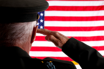 Senior military man in uniform saluting the 50 star American flag.